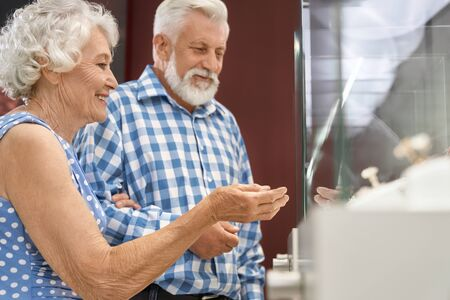 Smiling senior woman in elegant polka dot dress holding by hand her bearded old husband and pointing finger to showcase in luxury jewelry store. Concept of shopping, sale and consumerism Zdjęcie Seryjne