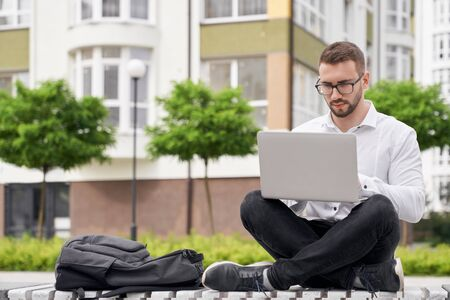 Handsome, young bearded man sitting on bench with crossed legs, holding laptop on knees. Stylish student in glasses looking at laptop, working, browsing. Backpack on bench. Stock Photo