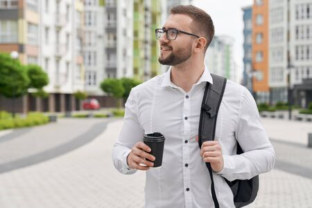 Close up of young bearded student with backpack on shoulder standing with black coffee cup, looking on building. Handsome man in glasses posing on background of multistory houses.