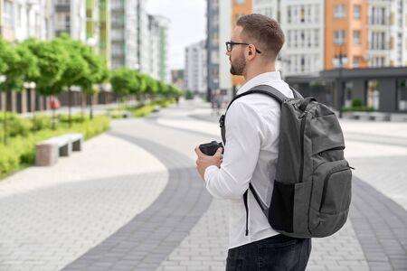 Giovane uomo barbuto con zaino sulle spalle in piedi vista laterale con tazza di caffè. Bell'uomo con gli occhiali che indossa in camicia bianca alla ricerca di case a più piani. Archivio Fotografico