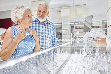 Cheerful bearded senior man in checkered shirt embracing his beautiful wife in blue dress that trying on pearl necklace at jewelry store. Grey haired husband doing pleasant present to beloved woman Zdjęcie Seryjne