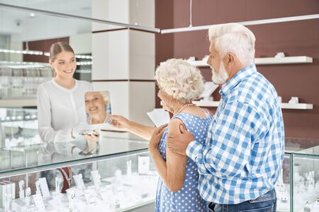 Grey haired man in checkered shirt standing behind his beautiful wife in blue dress embracing her while she trying on amazing pearl necklace at shopping mall. Concept of shopping, sale and consumerism