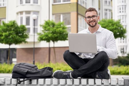 Handsome, positive man in glasses sitting on bench with crossed legs, looking at camera, smiling. Young freelancer working outdoor in city near multistory houses, using laptop.
