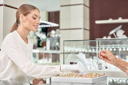 Side view of blonde smiling attractive female jeweler in white blouse and gloves recommending gold products to customer at jewelry store. Experienced consultant proficiently servicing clients
