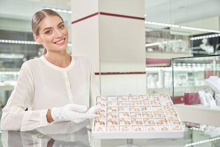 Beautiful female jeweler smiling, looking at camera and standing behind the showcase showing collection of wedding rings at luxury store. Helpful assistant professionally performing her job
