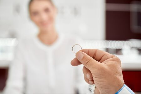 Close up of golden wedding ring that holding mans hand with blur background behind in jewelry store. Senior man buying new accessory that competent female seller advised him