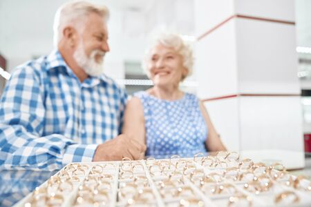 Cheerful aged couple in stylish clothing sitting at the table in jewelry store and pleasantly surprised of beautiful collection of gold rings. Concept of customer service and purchase.