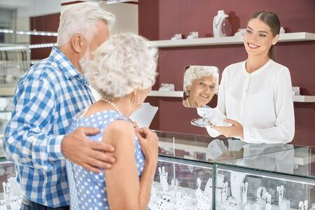 Friendly charming female seller with blond hair that tied in knot, wearing white blouse and gloves, holding mirror in which looking cute senior lady that admiring luxurious necklace on her neck. Фото со стока