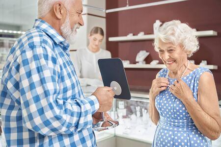 Careful husband with grey hair and beard expressing his love to charming happy wife by buying new luxury necklace at jewelry store. Mature couple enjoying shopping time together