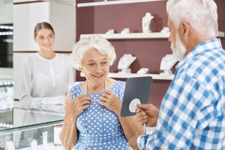 Happy aged woman with grey curly hair in blue trendy dress smiling to her bearded senior husband while choosing luxury pearl necklace at jewelry market. Mature married couple making precious purchase