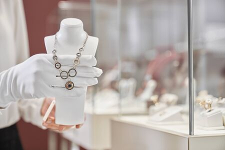 Close up of female consultant hands in white gloves presenting expensive gold, silver necklace in jewelry store. Professional seller showing precious goods for customers Zdjęcie Seryjne