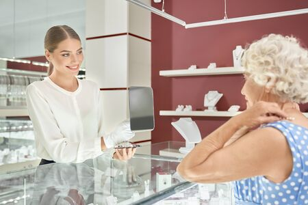 Friendly blonde female seller in white blouse and gloves holding mirror and helping demanding senior lady to choose exclusive necklase. Professional consultant servicing customers with high quality Reklamní fotografie