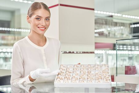 Beautiful smiling blonde female seller in white blouse and gloves standing behind the showcase and demonstrating the variety of wedding rings at jewelry store. Concept of professional assistant Reklamní fotografie