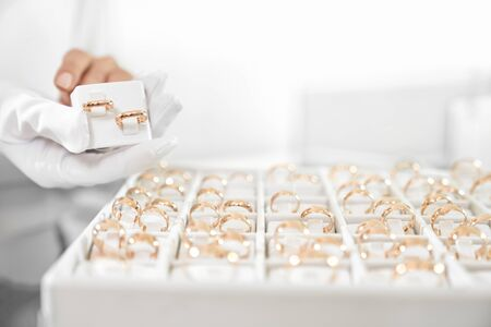 Close up of woman hands in white gloves showing collection of wedding rings at jewelry store. Female worker doing professional consulting for demanding clients. Customer service concept