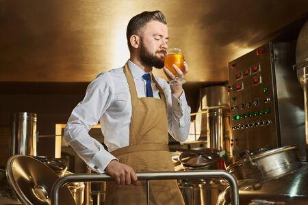 Vista dal lato del birraio maschio annusare una deliziosa birra dorata mentre si lavora in fabbrica. Uomo barbuto in piedi in un moderno birrificio e produzione di birra. Concetto di produzione e distillazione.
