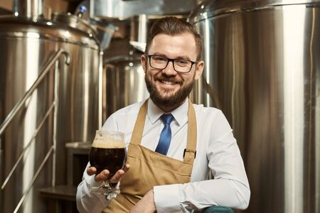 Front view of cheerful man wearing white shirt and apron looking at camera and laughing while keeping glass of root beer. Professional brewer enjoying delicious dark ale. Concept of production.