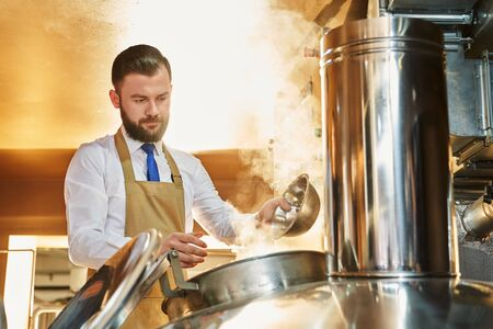 Serious man brewing beer. Professional brewer in white shirt and apron working in beer manufacturing factory and controlling process of ale production. Concept of distillery and beverage. Stockfoto