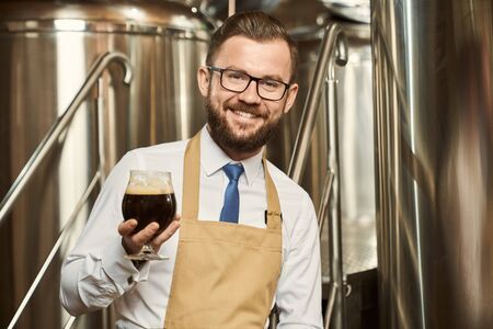 Front view of happy bearded male brewer keeping glass of dark beer in hand, looking at camera and smiling. Man working in brewery and examining quality of ale. Concept of manufacturing.