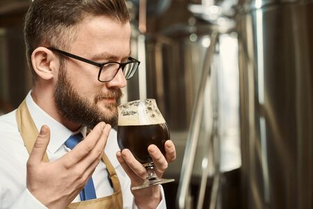 Closeup of bearded man in glasses smelling tasty dark beer after brewing. Professional male brewer tasting ale and examining quality of beverage. Concept of manufacturing and craft.