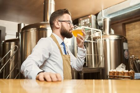 Side view of young male brewer in white shirt and apron standing in brewery and drinking tasty golden ale. Bearded man in glasses tasting beer after brewing. Concept of production and beverage.