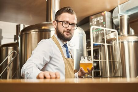Young bearded brewer looking at camera and smiling while keeping glass of golden ale in hand. Man wearing white shirt and apron standing in brewery and examining beer. Concept of production. Stockfoto