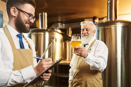 Two brewers standing in brewery and examining quality of ale. Bearded man keeping glass of beer while colleague keeping folder and writing down data. Concept of manufacturing.