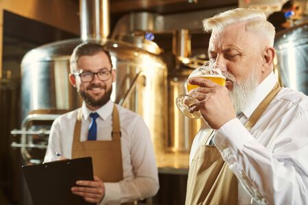 Side view of bearded brewer keeping glass of beer and drinking tasty beverage at manufacturing factory. Happy colleague keeping folder, writing and smiling at background. Concept of ale.