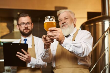 Two professional men wearing white shirts and aprons keeping glass of light beer and examining quality of alcohol. Colleagues looking at drink and writing in folder. Concept of brewery.