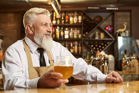 Side view of bearded man wearing white shirt and apron looking forward while keeping glass of light beer in hand. Male brewer standing over bar and smiling. Concept of beverage and drinking.