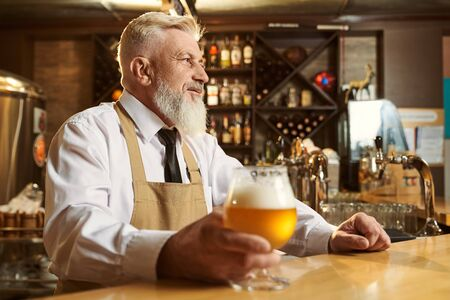 View from side of nice man wearing white shirt and apron standing over bar and drinking light beer. Professional male brewer looking forward and keeping glass of alcohol. Concept of beverage.