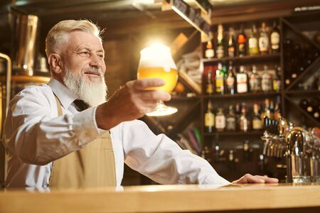 Selective focus of cheerful man in white shirt and apron standing over bar and keeping glass of light beer. Man looking forward and smiling while toasting with mug. Concept of brewery.