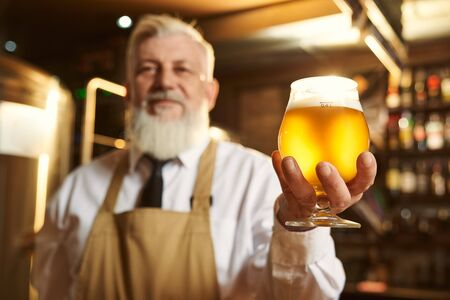 Selective focus of glass of light beer in hands of elder man. Professional brewer in white shirt and apron standing and smiling at background. Concept of alcohol and production.