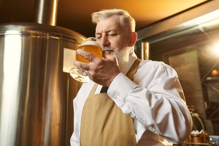 Front view of elder man in white shirt and apron standing in brewery and tasting beer. Man keeping glass and drinking delicious light alcohol. Concept of quality and production.