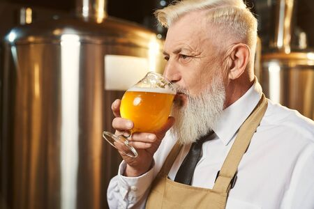 View from side of bearded man wearing white shirt and apron standing in brewery and tasting light beer. Male brewer keeping glass of delicious golden ale and drinking alcohol. Concept of beverage.