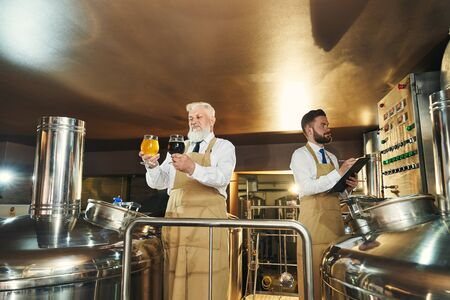 Two men in white shirts and aprons standing in beer manufacturing factory. Male brewers working, looking at dark and light ale and examining quality of beverage. Concept of production.