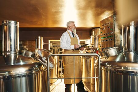 Side view of professional male brewer keeping folder and controlling beer production. Man in apron working in brewery and examining quality of ale. Concept of distillation and beverage.