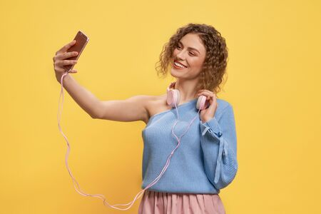 Pretty, young charming model with pink headphones holding phone in elongated hand, doing selfie. Glamour, positive girl with one bare sholder smiling, looking at phone, posing on yellow background.