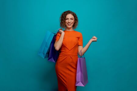 Front view of happy woman looking at camera and smiling while keeping colorful paper bags on blue isolated background. Young customer shopping and buying new clothes. Concept of happiness. 版權商用圖片