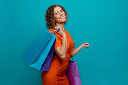 Side view of attractive girl in orange dress looking at camera after shopping on blue isolated background. Positive woman keeping paper bags with purchases, posing and smiling. 版權商用圖片