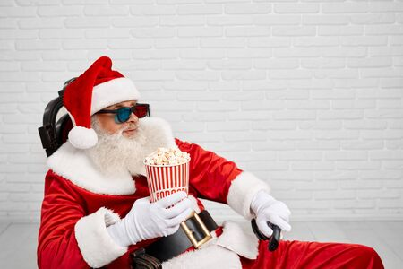 Side view of relaxed Santa Claus with grey beard wearing traditional costume and 3d glasses, sitting comfortable in chair and holding bucket with popcorn in one hand and TV zapper in another hand. 版權商用圖片