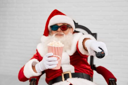 Portrait of Saint Nicholas in red and white costume sitting in armchair, watching TV in 3d glasses and using zapper to switch channels. Elder man with grey beard eating popcorn and enjoying movie.