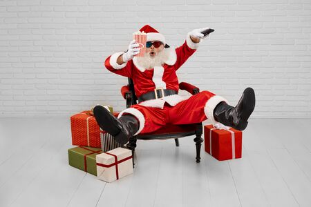 Happy Santa Claus with open mouse snuggled down in comfortable chair and is going to watch TV with tasty popcorn. Christmas character in 3d glasses posing in white studio with boxes of presents 版權商用圖片
