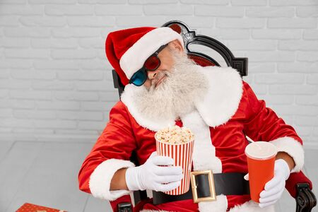 Tired traditional christmas character in red costume sleeping in comfortable armchair with popcorn and cola in hands. Mature Santa Claus taking nap before giving gifts to happy children. 版權商用圖片