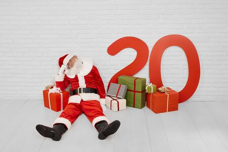 Tired mature Santa Claus sitting on white floor near red big gift box with paper numbers of 2020 New Year. Christmas time, happy holidays and traditions.