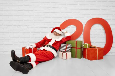 Beautiful white studio with cheerful Santa Claus in traditional costume lying on white floor with lots of gift boxes and paper red colored numbers 20. Concept of happy new year and christmas time