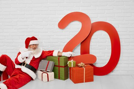 Senior male christmas character in red costume sitting on white floor with gift boxes and paper colored numbers of 20. Santa Claus with presents in white studio 版權商用圖片