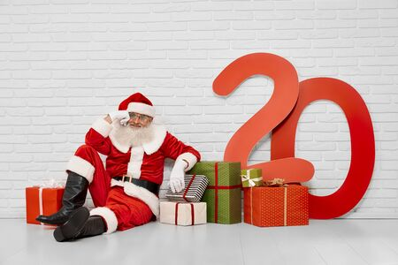 Thoughtful senior Santa Claus in glasses and white gloves, looking away and sitting on white floor with colorful presents and paper numbers of 20. Concept of christmas time and traditions