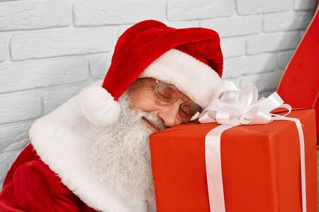 Senior kind Santa Claus with gray beard sleeping on red gift box with white wall behind. Christmas character in traditional costume tired after giving presents to happy children. Banco de Imagens