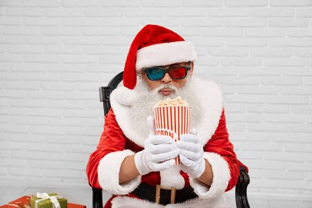 Portrait of Santa Claus wearing 3d glasses, white gloves and red hat, sitting in armchair and looking at striped bucket of popcorn that keeping in hands with background of white wall