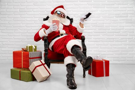 Cheerful Santa Claus in traditional costume, white gloves and 3d glasses sitting comfortably in armchair and holding bucket with popcorn and TV zapper. Concept of christmas time and celebration 版權商用圖片
